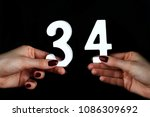 Small photo of On a black background, female hand with number thirty-four.