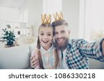 Small photo of Self portrait of attractive cheerful joyful family with one parent shooting selfie on front camera, cute kid and stylish daddy wearing crowns on heads having video-call, with mother