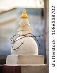 Small photo of The Buddhist stupa entangled by a barbed wire, as symbol of restriction of religious freedoms of Buddhists.