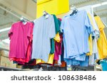 Variety of color t-shirts on stand in supermarket - stock photo