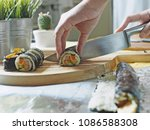 Woman hand using sharp knife to slice Korean seaweed rice roll or kimbap sometimes spelled gimbap over wooden cutting board with some sliced kimbap and blurred cactus plant pots and aluminium foil.