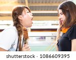 Stock photo lovely girl is using hand close her nose because her friend persecute and blow her bad breath to 1086609395