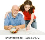 Small photo of Confused senior man trying to fill out an absentee ballot with his granddaughter's help. Isolated on white.