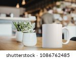 Small photo of White coffee Mug Mockup set-up in a cafe, next to cactus plants and with blurred background. Great for overlaying your custom quotes and designs for selling mugs.