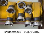 Zoomed yellow firehose are hanging on warehouse  shelfs - stock photo