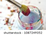 paint brush in water jar with... | Shutterstock . vector #1087249352