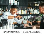 Stock photo mixed race male expert bartender is serving some tonic for a cocktail at the bar counter while a 1087608308