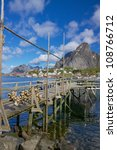 Wooden pier in town of Reine on the coast of fjord on Lofoten islands - stock photo
