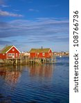 Red fishing rorbu huts by the fjord in town of Reine on Lofoten islands - stock photo