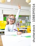 Small photo of At school - Happy schoolchild raising hand in classroom