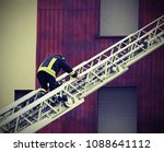 Small photo of One fireman walks on the aerial ladder with vintage effect
