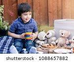 cute little boy sitting with...   Shutterstock . vector #1088657882