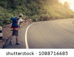 Small photo of Travel man hitchhiking. A hitchhiker by the road during vacation trip in mountains at sunset. The concept of traveling and hitchhiking.