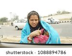 Small photo of Delhi, India, 6 February 2018, The woman beggar with newborn baby come to car for beg some money. Pity baby.