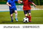 young boys playing soccer... | Shutterstock . vector #1088983025