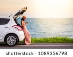 Stock photo happy alone young woman traveler on the beach road with white hatchback car with hand holding 1089356798
