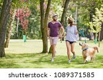 Stock photo lovely young couple running in the park with their dog during summer 1089371585