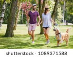 young couple walking their dog... | Shutterstock . vector #1089371588
