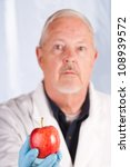 "Small photo of Doctor holding out an apple suggesting the old adage ""An apple a day will keep the Doctor away"""