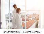Stock photo young happy couple in hotel room in the morning just married man and woman standing at window 1089583982
