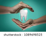 a tooth between two palms of a... | Shutterstock . vector #1089698525