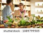 happy shop assistant giving...   Shutterstock . vector #1089799505