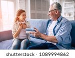 the happy grandfather giving a... | Shutterstock . vector #1089994862
