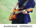 Close-up view at guitar in girl's hands at outdoor. - stock photo