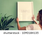 girl hanging a frame on a green ... | Shutterstock . vector #1090184135