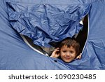 a refugee boy sits in tent in... | Shutterstock . vector #1090230485