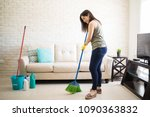happy young maid sweeping floor ... | Shutterstock . vector #1090363832