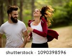 young couple jogging outdoors... | Shutterstock . vector #1090398596