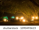 Tent and campsite at night lit by lanterns and colored led lights in a forest - stock photo