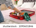 young woman packing suitcase on ...   Shutterstock . vector #1090631846