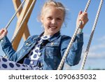 a teenage girl swinging on a... | Shutterstock . vector #1090635032