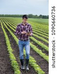 Small photo of Young handsome farmer with tablet walking in soybean field in spring. Agribusiness and innovation concept