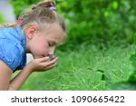 a girl in blue clothes sniffing ... | Shutterstock . vector #1090665422