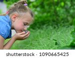 a girl in blue clothes sniffing ... | Shutterstock . vector #1090665425