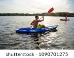 young man paddling kayak on the ... | Shutterstock . vector #1090701275