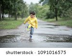 Small photo of A wet child is jumping in a puddle. Fun on the street. Tempering in summer. Splashes, drops of water, outdoor. waterproof boots jump in puddle and mud in the rain.