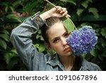 woman hold blue hydrangea at...   Shutterstock . vector #1091067896
