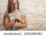 Stock photo favorite kitten girl is holding a red kitten little funny red cat biting fingers girl playfully 1091080082