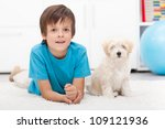 Young boy and his good behaving doggy together indoors - stock photo