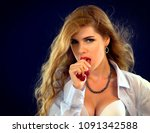 Small photo of Woman eating berry. Female libido wearing unbuttoned business blouse and bra looking seductively with passion. Pin up female style. Soft light effect on black background.