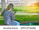 a woman is sitting on a bench... | Shutterstock . vector #1091376686