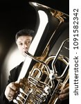 Small photo of Tuba player. Trumpeter playing horn brass instrument closeup.