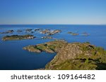 Scenic town of Henningsvaer on Lofoten islands in Norway with large fishing harbor and bridges connecting rocky islands - stock photo
