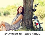 Beautiful girl sitting near bike and tree at rest in forest. Photo in retro style. - stock photo