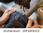 Small photo of Sewing denim jeans with sewing machine. Repair jeans by sewing machine. Alteration jeans, handmade garment industrial concept.