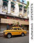 Small photo of Kolkata, India - March, 2014: Vintage classic Ambassador taxi car on the street in historical district in Calcutta. Yellow cab parked in a front of colonial building.
